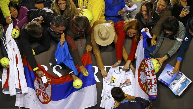 Djokovic of Serbia signs autographs after defeating Muller of Luxembourg in their men's singles match at the Australian Open 2015 tennis tournament in Melbourne