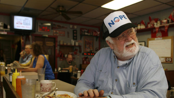 This photo taken Oct. 26, 2012 shows Hank Wessel, 68, talking with another customer at the Sunbury Grill in Sunbury, Ohio. He wears his allegiance on his hat and spoke about what it is like to be bombarded by all the political ads this time around. (AP Photo/Mike Munden)