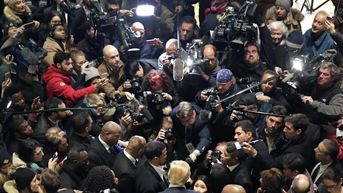 Republican presidential candidate Donald Trump, foreground center, stands in the middle of a media crush in the Trump Tower lobby in New York, Monday, Nov. 30, 2015. Trump met with a coalition of 100 African-American evangelical pastors and religious leaders in a private meeting at Trump Tower. (AP Photo/Richard Drew)