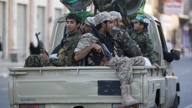 Houthi Shiite fighters wearing an army uniform ride on a pickup vehicle as they patrol a street during a demonstration to show support for their comrades in Sanaa, Yemen, Friday, Jan. 23, 2015. Thousands of protesters demonstrated Friday across Yemen, some supporting the Shiite rebels who seized the capital and others demanding the country's south secede after the nation's president and Cabinet resigned. (AP Photo/Hani Mohammed)