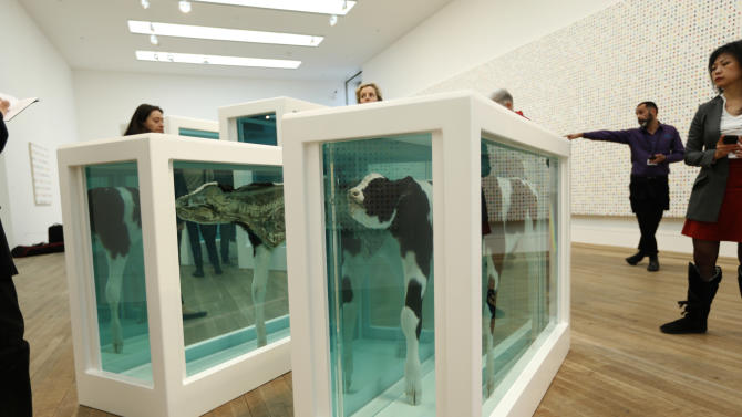 """People look at part of the British artist Damien Hirst's 2007 exhibition copy piece of the 1993 original """"Mother and Child Divided"""", composed of a cow and a calf sliced in half in glass tanks of formaldehyde, during a media preview of the first substantial survey show of his work in the UK at the Tate Modern gallery in London, Monday, April 2, 2012.  The exhibition, timed for the culmination of the Cultural Olympiad and due to open to the public on Wednesday, showcases over 70 of Hirst's works since he first came to public attention in 1988.  (AP Photo/Matt Dunham)"""
