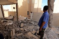 Libyan men inspect a destroyed building in Bani Walid on October 11. Ex-rebels allied to Libya's army attacked a bastion of diehards linked to slain dictator Moamer Kadhafi in clashes that left at least 11 dead, underlining the challenges facing the government