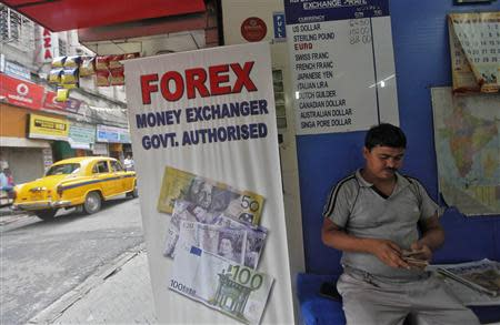 A customer counts currency inside a currency exchange shop in Kolkata