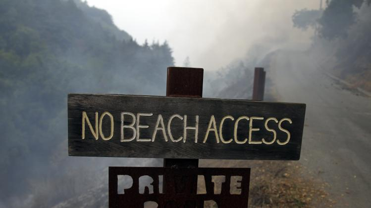 Signs are posted at the entrance to the access road leading to Pfeiffer Ridge during a wildfire in Big Sur