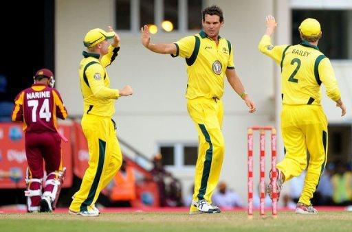 Australian cricketer Clint McKay (C) celebrates with teammates after dismissing West Indies batsman Sunil Narine (L)