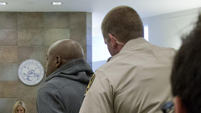 Floyd Mayweather Jr., left, is handcuffed by court marshal Ron Johnson, Friday, June 1, 2012, in Las Vegas, to begin a 90-day jail term for attacking his ex-girlfriend in September 2010 while two of their children watched. The undefeated five-division champion surrendered Friday before the judge who sentenced him in December, and then allowed him to remain free long enough to headline a May 5 fight. (AP Photo/Julie Jacobson)