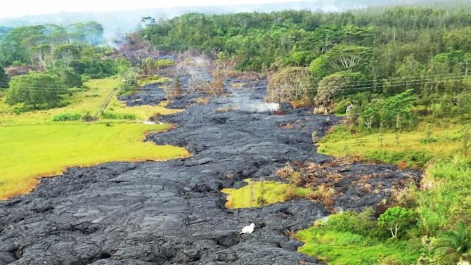 This Oct. 28, 2014 photo provided by Pete Stachowicz of Paradise Helicopters shows a lava flow near the town of Pahoa on the Big Island of Hawaii. The National Guard is deploying troops to the rural Hawaii town as lava makes a slow crawl toward a major road and threatens to further isolate the community that got its start during the lumber- and sugar-plantation heydey. Hawaii County Civil Defense Director Darryl Oliveira said Thursday, Oct. 30, 2014, the National Guard is deploying 83 troops to Pahoa to help provide security. The troops will help with a roadblock and with other safety issues. (AP Photo/Pete Stachowicz, Paradise Helicopters)