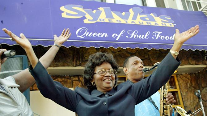 """FILE- In this Aug. 1, 2002 file photo, Sylvia Woods, center, moves to the music outside her restaurant, """"Sylvia's,"""" during the restaurant's 40th anniversary celebration, in the Harlem neighborhood of New York. Woods died in Mount Vernon, N.Y. on Thursday, July 19, 2012. She was 86. (AP Photo/Stuart Ramson, File)"""