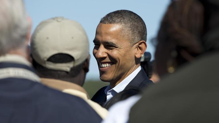 President Barack Obama greets people on the tarmac as he arrives at Newport News Williamsburg International Airport on Air Force One, Saturday, Oct. 13, 2012, in Williamsburg, Va. (AP Photo/Carolyn Kaster)