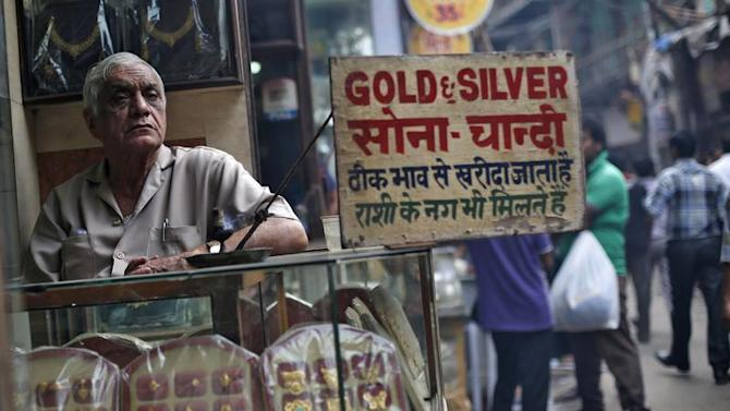 A shopkeeper waits for customers at his gold and silver jewellery shop in Delhi