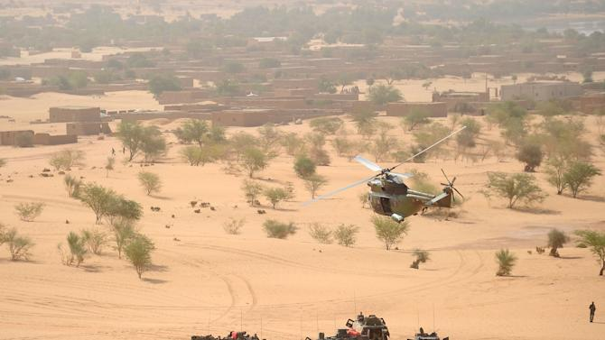 A Puma helicopter flies above French military vehicles near Bourem, northern Mali, Sunday, Feb. 17, 2013. Mali's military detained eight Arab men last week in Timbuktu, raising fears of further reprisals against the region's Arab minority whose members are accused of having supported the al-Qaida-linked groups which overran northern Mali last year. (AP Photo /Pascal Guyot, Pool)