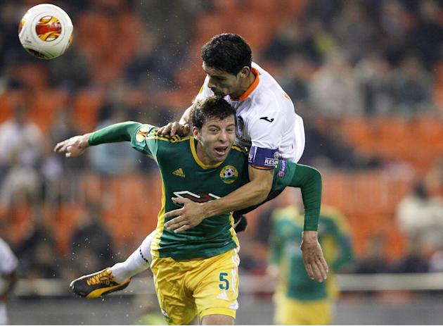 Kuban Krasnodar's Angel Dealbert from Spain, foreground,  duels for the ball with Valencia's Ricardo Costa, from Portugal, during their  Europa  League Group A soccer match at the Mestalla sta