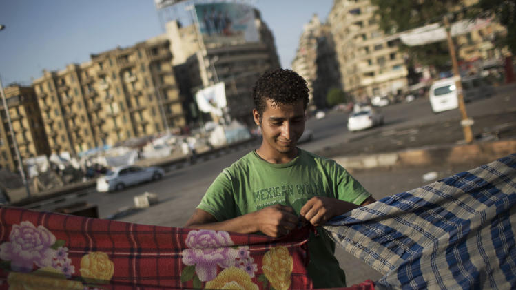 An Egyptian man builds his tent at Tahrir Square where a few protesters have built their camp protesting against the release of Egypt's ousted President Hosni Mubarak in Cairo, Egypt, Saturday, Aug. 24, 2013. (AP Photo/Manu Brabo)