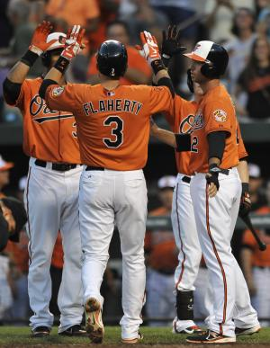 Baltimore Orioles' Ryan Flaherty is congratulated by team mates, Chris Dickerson, left, and J.J. Hardy, right, after hitting a three-run home run against the New York Yankees in the third inning of a baseball game, Saturday, June 29, 2013, in Baltimore. (AP Photo/Gail Burton)