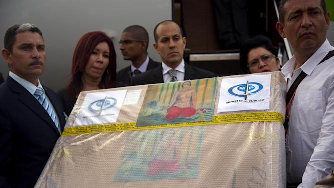 """Venezuelan government handlers hold a package containing the painting """"Odalisque in Red Pants,"""" by Henri Matisse, stolen more than a decade ago from a museum in Venezuela, at the airport in Caracas, Monday, July 7, 2014. Venezuelan authorities say the 1925 painting was stolen from the Caracas museum in 2000. The original work was swapped out for a copy. It was found in July 2012 when a couple tried to sell it to undercover FBI agents at a hotel in Miami Beach. The two were sent to prison for attempting to sell the stolen work. (AP Photo/Ramon Espinosa)"""