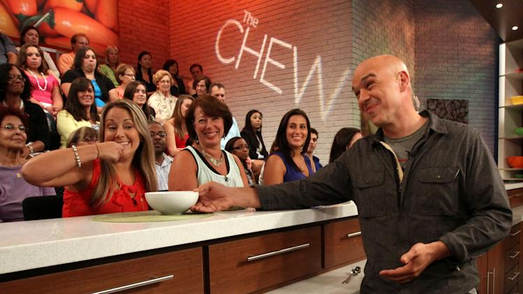 "This Friday, Aug. 26, 2011 photo shows Iron Chef Michael Symon, co-host of ABC's ""The Chew"", right, as he runs through a tasting segment with members of the audience during a rehearsal for the show in New York. Can some of food and style TV's biggest stars help ABC soap fans get over cancellation of their favorite stories? The network's counting on it for ""The Chew.""     (AP Photo/Tina Fineberg)"