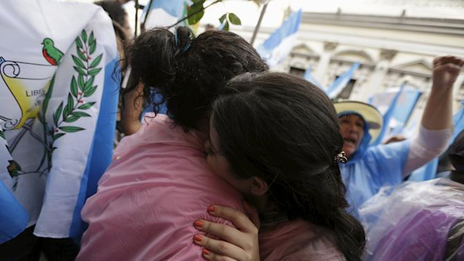Women embrace outside of the Guatemalan Congress building after the congress voted to strip Perez of immunity, in Guatemala City