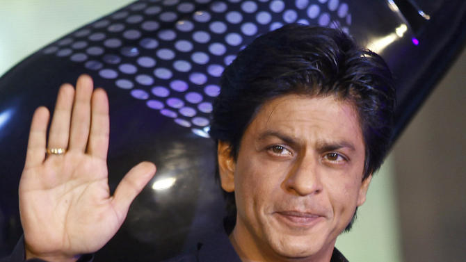 FILE - In this Tuesday, Jan. 29, 2013 file photo, Bollywood actor Shah Rukh Khan waves during the unveiling of TOIFA Bollywood awards in Mumbai, India. Khan has been caught in a verbal slugfest between India and Pakistan after he wrote a magazine article that led to heated exchanges between the rival nations. Pakistan's Interior Minister Rehman Malik suggested that New Delhi beef up the actor's security after Khan wrote an account of how it felt to be a Muslim in India. (AP Photo/Rafiq Maqbool, File)