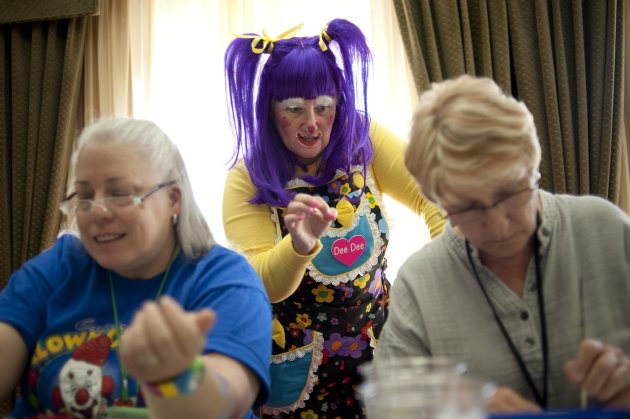 "In a July 31, 2012 photo, Deanna Hartmier, aka ""Dee Dee"" the clown, center, offers tips to Patricia Jannell, aka ""PJ"" the clown, and Carol Feldhelm, aka ""Dizzy Daizy"" the clown, during a face painting class at the third annual Clown Campin' in Ontario, Calif. The week long event is held for clowns across the United States and Canada to learn, get inspired, and network. (AP Photo/Grant Hindsley)"
