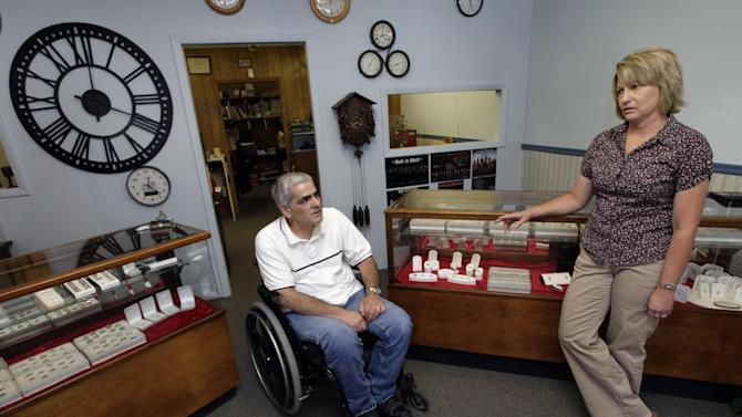 In this Thursday, June 14, 2012 photo, Mike Lamm talks with his wife Tracey in the showroom of his jewelry shop in Mediapolis, Iowa. These days, people aren't buying much jewelry. What saves him is his ability to repair watches and make rings. There's still enough call for that kind of work in the small town in rural southeastern Iowa. When the government reported that the Great Recession claimed nearly 40 percent of Americans' wealth, the figure alarmed economists. But for families across the country, the numbers merely confirm that they are not alone. (AP Photo/Charlie Neibergall)