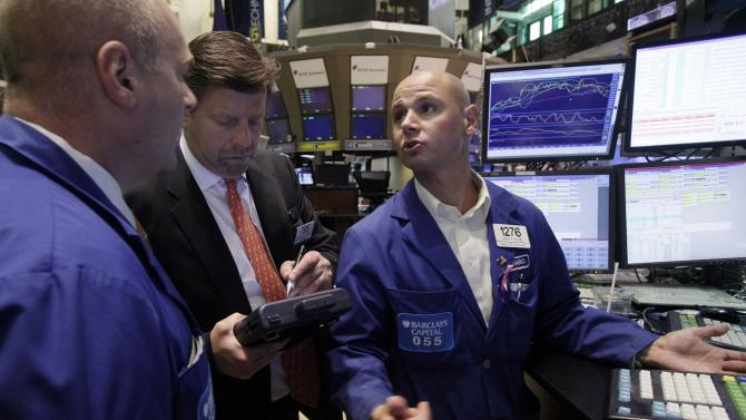 Mario Picone, right, talks with fellow specialist Evan Solomon, left, as trader Edward Schreier works on his handheld device, on the floor of the New York Stock Exchange Friday, June 3, 2011. (AP Photo/Richard Drew)