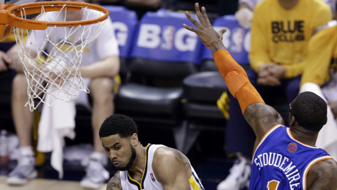 Indiana Pacers guard D.J. Augustin, left, attempts a pass to center Roy Hibbert under New York Knicks forward Amar'e Stoudemire (1) during the second quarter of Game 6 of the Eastern Conference semifinal NBA basketball playoff series in Indianapolis, Saturday, May 18, 2013. (AP Photo/Michael Conroy)