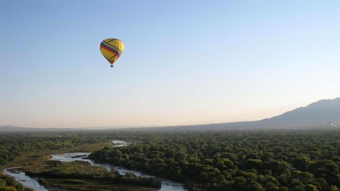 This Oct. 1, 2012 photo shows a balloon gliding over the waters of the Rio Grande river and its forested shores in Albuquerque, N.M. With most days offering sunny, clear weather in Albuquerque, the city has become known for its balloon rides, including its annual International Balloon Fiesta. (AP Photo/Beth Harpaz)