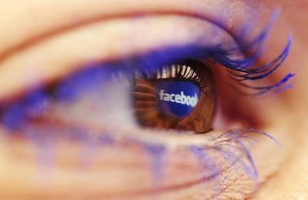 A Facebook logo reflected in the eye of a woman is seen in this picture illustration