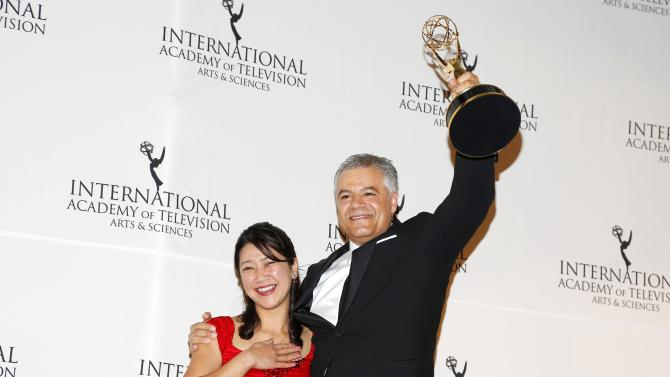 """Producer/director Damon Vignale and producer Miho Yamamoto of the documentary """"The Exhibition"""" pose backstage with their award for Arts Programming at the 42nd International Emmy Awards in New York"""