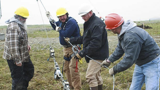 This July 2, 2011 photo provided by the U.S. Coast Guard shows Richard Belisle, second from left, and Coast Guard Petty Officer 1st Class James Hopkins, second from right, are seen with Jim Wells, left, and Coast Guard Petty Officer 3rd Class Cody Beauford as they help erect a communications antenna on Shemya Island, Alaska.  After more than 24 hours, no suspect has been identified after someone shot to death the two men at a CoastGuard communications station  on Kodiak Island off Alaska's mainland . (AP Photo/U.S. Coast Guard)