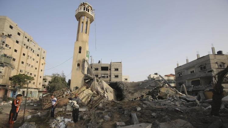 Palestinians survey the rubble of a mosque, which police said was destroyed in an Israeli air strike, in Nuseirat in the central Gaza Strip