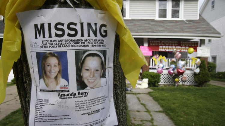 A missing poster still rests on a tree outside the home of Amanda Berry Wednesday, May 8, 2013, in Cleveland. Berry, 27, Michelle Knight, 32, and Gina DeJesus, had apparently been held captive in a house since their teens or early 20s, police said. (AP Photo/Tony Dejak)