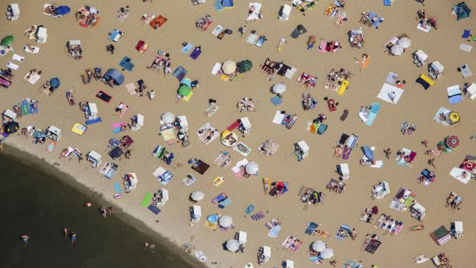 People swim and sunbathe on a hot sunny summer day at the beach of Wannsee near Berlin