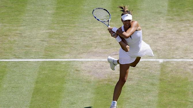 Garbine Muguruza of Spain returns a ball to Timea Bacsinszky of Switzerland during their singles match at the All England Lawn Tennis Championships in Wimbledon, London, Tuesday July 7, 2015. (AP Photo/Kirsty Wigglesworth)