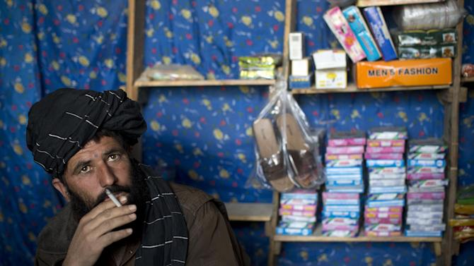 In this Oct. 21, 2012 photo, shop owner Mohammed Haider enjoys a cigarette while waiting for customers at a local bazaar in Marjah, Helmand province, Afghanistan. Haider explains that poppy farmers who planted substitute crops are losing money because they can't sell their harvests. He predicts poppy production would double when foreign soldiers leave in 2014.  In southern Helmand province, one of Afghanistan's deadliest battlefields, angry residents say 11 years of war has brought them widespread insecurity. Development that was promised hasn't materialized and the Taliban's rule is often said to be preferred. (AP Photo/Anja Niedringhaus)