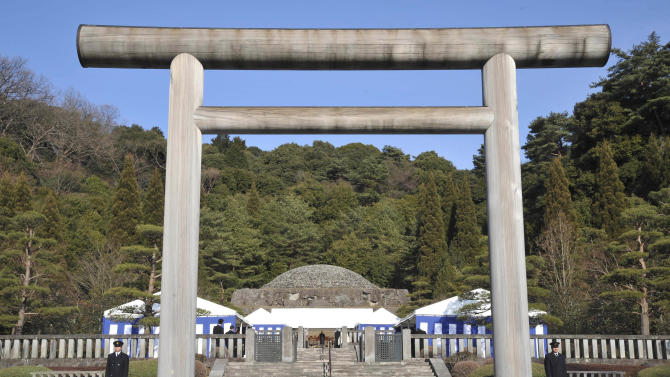 """FILE - In this Jan. 7, 2009 file photo, security officers stand guard near a """"torii"""" gate as Japan's Emperor Akihito, center, offers prayers at Musashino Imperial Mausoleum in Hachioji in the western suburbs of Tokyo, marking the 20th anniversary of late Emperor Hirohito's death. Akihito, turning 80 on Monday, Dec. 23, 2013 is still active, making an official visit to India in November with his wife, the 79-year-old Empress Michiko. But concerns have grown since he had heart bypass surgery nearly two years ago on top of prostate cancer earlier. After an expert panel discussion for more than a year, the palace announced that Akihito will be cremated, and his remains placed in a mausoleum smaller than those of his predecessors, with Michiko's by his side at the Imperial compound in western Tokyo. Akihito's cremation breaks a 400-year burial custom of the world's oldest monarchy, as he wishes to trim cost, space and burden on the people, officials said. (AP Photo/Katsumi Kasahara, File)"""
