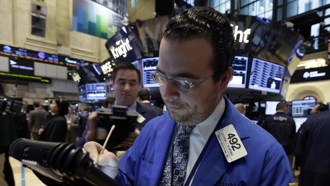 In this Friday, March 15, 2013, photo, Trader Richard Scardino, right, uses his handheld device as he works on the floor of the New York Stock Exchange. World markets were lower Friday March 22, 2013 because of uncertainty over the restructuring of troubled banks in Cyprus.  (AP Photo/Richard Drew)