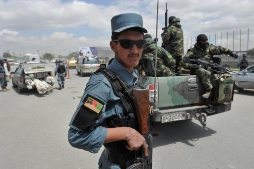 File photo shows an Afghan policeman guarding a checkpoint as commandos ride past in Kabul. A remote-controlled bomb attack by Taliban insurgents in the Afghan capital Kabul killed eight people