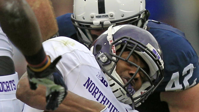 Northwestern running back Venric Mark, center, is tackled by Penn State linebackers Glenn Carson (40) and Michael Mauti (42) during the first quarter an NCAA college football game in State College, Pa., Saturday, Oct. 6, 2012. (AP Photo/Gene J. Puskar)