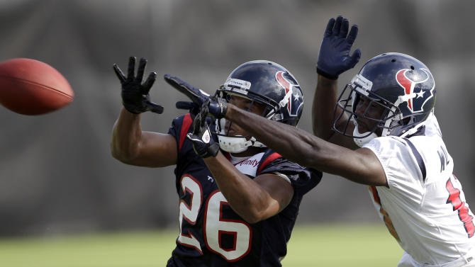 Houston Texans cornerback Brandon Harris (26) breaks up a pass intended for wide receiver Paul Williams, right, during an NFL football training camp practice Tuesday, Aug. 2, 2011, in Houston. (AP Photo/David J. Phillip)