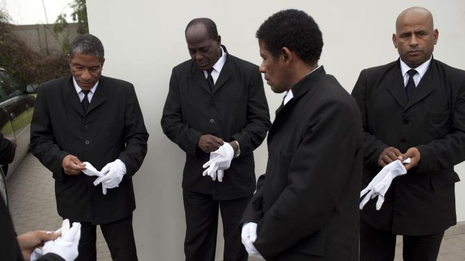 In this July 2, 2013 photo, black pallbearers put on their white gloves as they prepare to handle a coffin during a burial in Lima, Peru. These pallbearers are in the job precisely because of the color of their skin, a phenomenon unique to this South American capital that was a regional seat of Spain's colonial empire for more than three centuries and where racism remains so deeply ingrained that many Peruvians don't consider the practice discriminatory. (AP Photo/Rodrigo Abd)