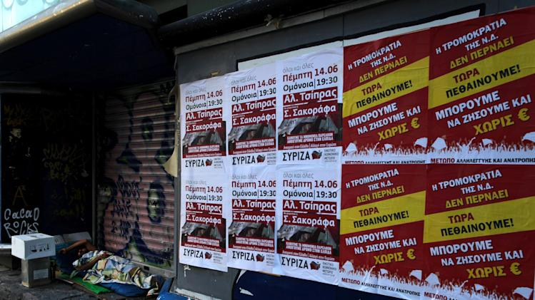 "A homeless man sleeps next  election posters, with far left political party, on right, reading ""we are dying now, we can live without Euro"", in central Athens, on Saturday, June 16, 2012.  Greeks cast their ballots this Sunday for the second time in six weeks, after May 6 elections left no party with enough seats in Parliament to form a government and coalition talks collapsed.(AP Photo/Petros Giannakouris)"