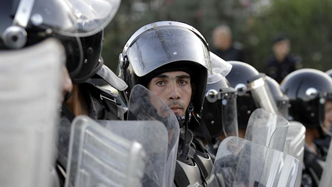 Jordanian policemen prepare to disperse protesters blocking a main road during a demonstration against a rise in fuel prices in downtown Amman, Jordan, Wednesday, Nov. 14, 2012. Hundreds of Jordanians chanted slogans against the king and threw stones at riot police as they protested in several cities for a second day Wednesday amid rising anger over fuel price hikes.(AP Photo/Raad Adayleh)