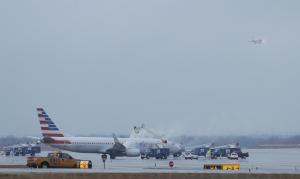 Crews spray deicing solution onto an American Airlines…