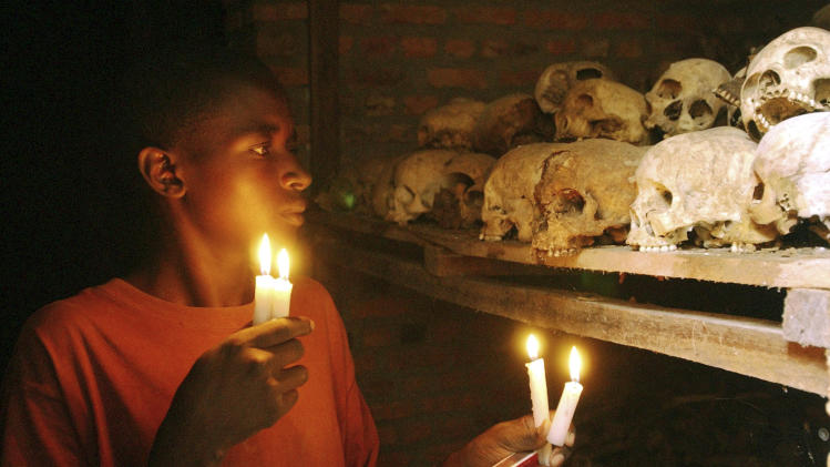 FILE - In this April 6, 2004 file photo, Apollan Odetta, a survivor from the 1994 Rwandan Genocide light candles at a mass grave in Nyamata, Rwanda. Two decades after the Rwandan genocide, France is finally opening what critics called its blind eye to justice over the killings. On Tuesday Feb. 4, 2014, a wheelchair-bound Rwandan former intelligence chief appears in Paris court for an expected seven-week trial to face charges of complicity in genocide and complicity in crimes against humanity. (AP Photo/Sayyid Azim, File)