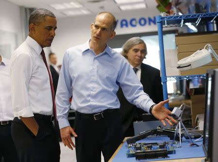 File photo of US President Obama listening to engineer Washington as he tours Vacon a company that manufactures AC drives during a visit to Raleigh North Carolina