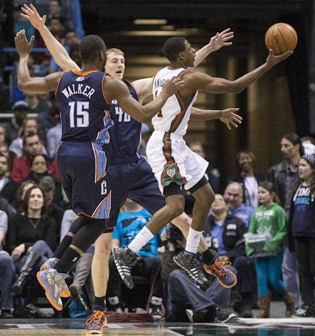 Milwaukee Bucks' Brandon Knight, right, drives between Charlotte Bobcats' Cody Zeller, center, and Kemba Walker (15) during the first half of an NBA basketball game on Sunday, March 16, 2014,