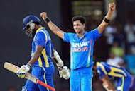 Indian cricketer Manoj Tiwary (centre) celebrates after he dismissed Sri Lankan cricketer Thisara Perera during the fourth one day international (ODI) match at the R. Premadasa stadium in Colombo. Tiwary grabbed four wickets to help India restrict Sri Lanka to 251-8 in the fourth one-day international in Colombo