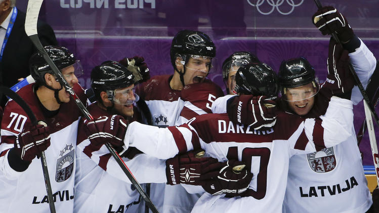 Latvia forward Lauris Darzins is congratulated by teammates after scoring against Switzerland in the third period of a men's ice hockey game at the 2014 Winter Olympics, Tuesday, Feb. 18, 2014, in Sochi, Russia. Latvia won 3-1 to advance to the quarterfinals. (AP Photo/Julio Cortez)