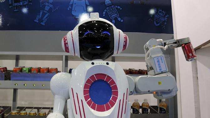 A sales assistant robot picks up a can of Coca Cola during a demonstration at the World Robot Conference in Beijing
